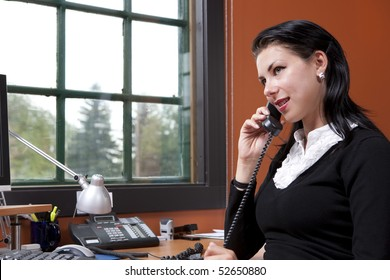 An attractive young businesswoman is sitting in front of a computer and smiling.  She is holding a phone to her ear. Horizontal shot.