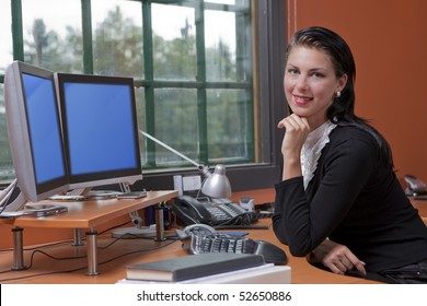 An attractive young businesswoman is sitting in front of a computer and smiling.  She is resting her chin on her hand. Horizontal shot.