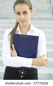Attractive young businesswoman smiling with a folder on his chest and a golden pen