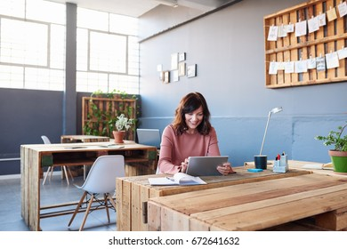 Attractive young businesswoman smiling while sitting alone at her desk in a modern office working online with a digital tablet
