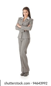 Attractive young businesswoman standing arms crossed, smiling, looking at camera.?