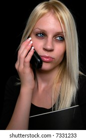 Attractive young businesswoman talking on the cell phone isolated ob black.