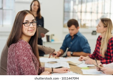 Attractive young businesswoman turning towards the camera with a friendly smile during a meeting with colleagues
