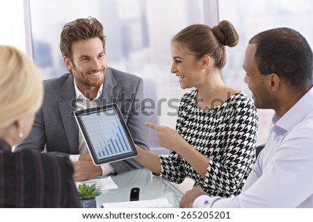 Attractive young businesswoman using tablet to present business diagram at a meeting.