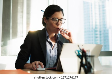 Attractive young businesswoman using a vaping device for nicotine addiction withdrawal symptoms. Stressed female executive vaping at work while using her laptop computer. Concept of Smoking Cessation