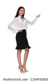 attractive young businesswoman wearing a black skirt is presenting to side while standing with a hand on hip on white background, full length picture