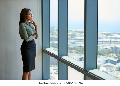 Attractive young businesswoman wearing glasses staring thoughtfully through office windows at the city skyline