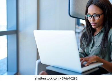 Attractive young businesswoman wearing glasses sitting in a chair in a modern office looking focused while working on a laptop