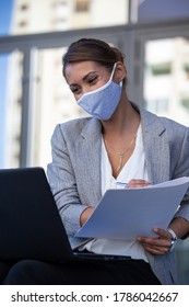 Attractive young businesswoman working on laptop in front of office building with protective mask on face, having conference meeting online