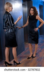 Attractive young businesswomen, waiting for lift, talking.