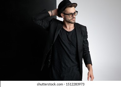 attractive young casual man wearing black hat, black coat and sunglasses, holding hand to head and looking to side, standing on black and white background in studio