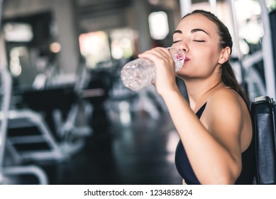 Attractive young Caucasian beautiful woman get resting and drink some water from plastic bottle after workout at gym