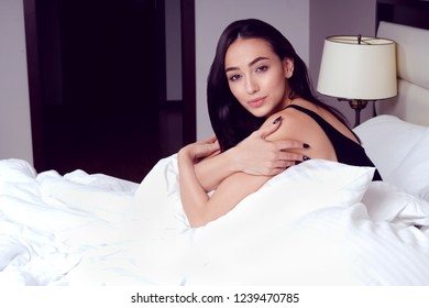 attractive young caucasian  beautiful woman at home sitting in bed morning looking at camera