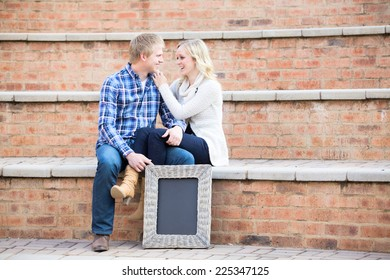 Attractive young caucasian couple in love, sitting on steps while smiling at each other