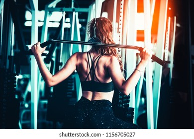 Attractive young caucasian girl in sport wear working out with fitness equipment in a professional gym. Confident young woman in fitness center. Training in gym, being fit and firm, sport concept.