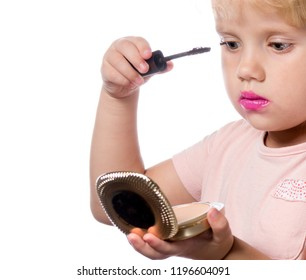attractive young caucasian little girl doing makeup applying mascara looking in the mirrow studio shot isolated on white