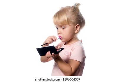 attractive young caucasian little girl doing makeup applying lıpstıck looking in the mirrow studio shot isolated on white