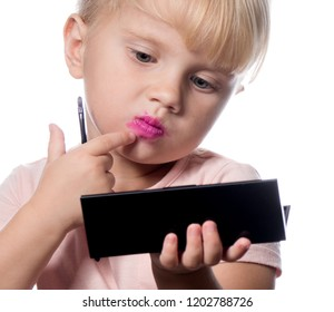 attractive young caucasian little girl doing makeup applying lıpstık looking in the mirrow studio shot isolated on white