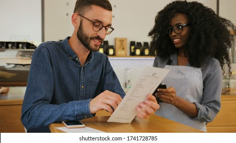Attractive young caucasian man making an order in the cafe in the african woman using menu, she writing down everything in notebook.
