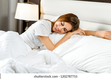 attractive young caucasian smiling cheerful woman at home lying in bed  sleeping eyes closed dreaming
