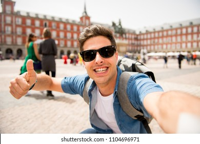 Attractive young caucasian tourist student man having fun happy and excited taking a selfie with smart phone in Plaza Mayor, Madrid, Spain. Travel,vacation, holidays in European city concept.