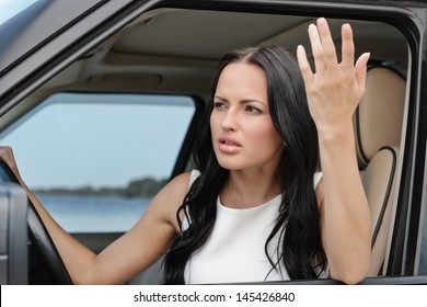 An attractive young Caucasian woman arguing with someone from the front seat of the car