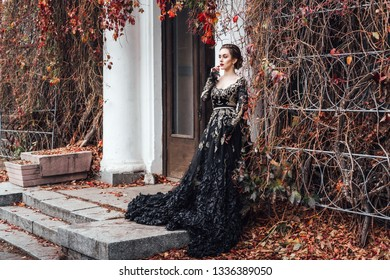 Attractive young caucasian woman in black evening long dress posing near entrance of old house entwined with red autumn foliage
