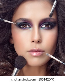 attractive young caucasian woman closeup portrait isolated on white looking at camera studio shot face macro skin makeup eyes hands brushes