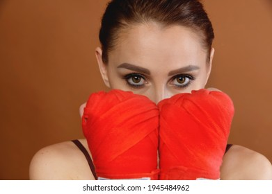Attractive young Caucasian woman, covering her face with boxing bandages wrapped around her hands, looks into the camera. Female wrestling concept. Fitness and female single combats