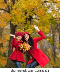 attractive young caucasian woman and girl in warm colorful clothing  with yellow leaves outdoors smiling