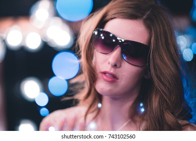 Attractive young caucasian woman poses with string lights with heavy bokeh