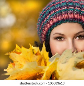 attractive young caucasian woman in warm colorful hat with yellow leaves outdoors smiling closeup portrait