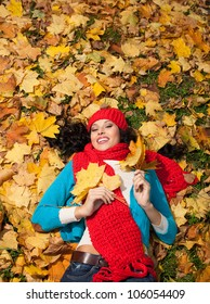 attractive young caucasian woman in warm colorful clothing luing down  on yellow leaves outdoors smiling - Shutterstock ID 106054409