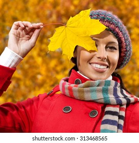 attractive young caucasian woman in warm colorful clothing  on yeloow leaves outdoors smiling