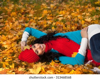 attractive young caucasian woman in warm colorful clothing  on yeloow leaves outdoors smiling lying down on grass
