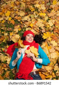 attractive young caucasian woman in warm colorful clothing luing down  on yellow leaves outdoors smiling - Shutterstock ID 86891542