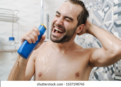 Attractive young cheerful man singing while washing in the shower, holding shampoo bottle