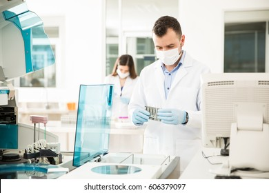 Attractive young chemists with lab coats and surgical masks running some blood tests in a laboratory