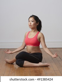 Attractive young Chinese model practicing yoga in studio.