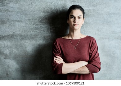 Attractive young christian woman in casual clothes leaning to wall. . Lifestyle portrait photo with copyspace.