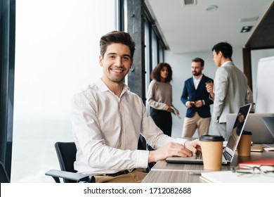 Attractive young confident businessman sitting at the office table with group of colleagues in the background, working on laptop computer