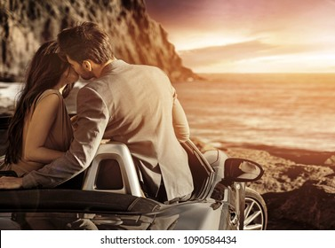 Attractive young cople kissing at sunset