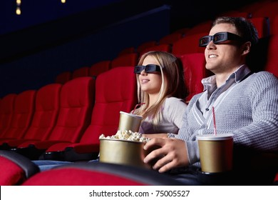 Attractive young couple in 3D glasses watching movies in cinema