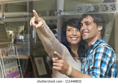 Attractive young couple agree and point at item in shop window
