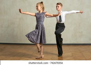 Attractive young couple of children dancing ballroom dance in studio