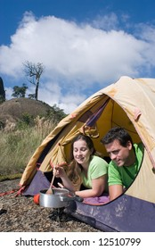 Attractive young couple cooking a meal in their tent. Shot is framed against a beautiful blue sky