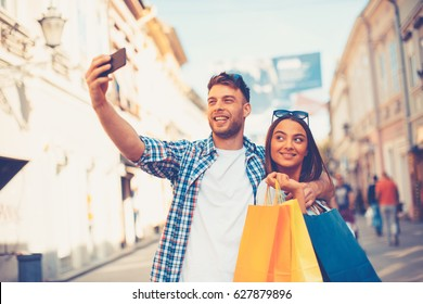 Attractive young couple doing selfi after shopping in downtown