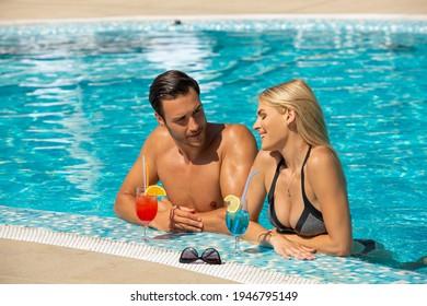 Atractiva pareja de jóvenes cócteles en la piscina del hotel