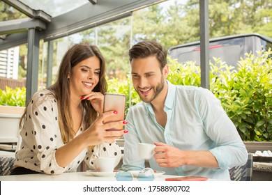 Atractiva pareja joven tomando café y viendo el teléfono inteligente en el restaurante del jardín