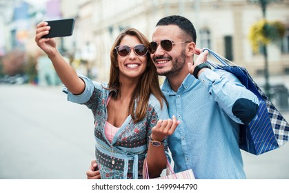 Attractive young couple enjoying in shopping, having fun in the city. Consumerism, love, dating, lifestyle concept